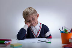 Sleepy little boy next to desk Stock Image