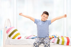 Sleepy little boy in pajamas stretching himself. Seated on a bed at home Stock Images