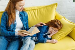 Sleepy little child listening to mother. Reading book royalty free stock image