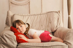 Sleepy little girl looking at camera in chair Royalty Free Stock Photo