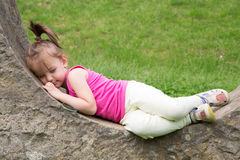 Sleepy Little Girl Resting On The Stonewall In The Park royalty free stock photography