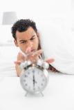 Sleepy man in bed extending hand to alarm clock Stock Image