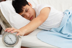 Sleepy man with clock Royalty Free Stock Photos