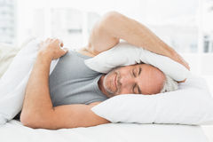 Sleepy man covering ears with pillow in bed Royalty Free Stock Photos