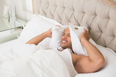 Sleepy man covering ears with pillow in bed Royalty Free Stock Photography