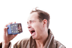 Sleepy man crying with alarm clock in hand in the early morning. Stock Photography