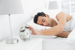 Sleepy man extending hand to alarm clock Stock Photo