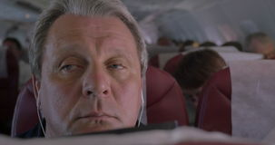 Sleepy man listening to music in airplane stock video