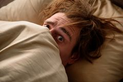 Scared guy unwilling to wake up at home. Sleepy man looking at camera with panic and lying in bed while covering his face with a blanket in bedroom. Close up Royalty Free Stock Images