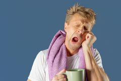 Sleepy man with a mug of coffee and a towel. Early morning stock images