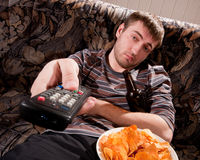 Sleepy man watching TV Stock Photography