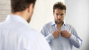Sleepy man wearing shirt, preparing for work in morning, unhappy with appearance royalty free stock image