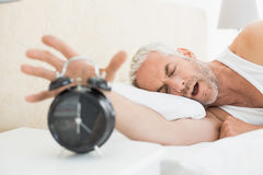 Sleepy mature man extending hand to alarm clock Stock Image