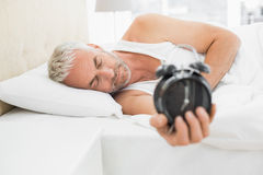 Sleepy mature man holding alarm clock in bed Royalty Free Stock Photography