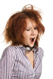 Sleepy music fan. A young woman with headphones around her neck is yawning, her mouth wide open Royalty Free Stock Images