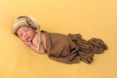 Sleepy newborn baby. One week old newborn baby of mixed race sleeping on a soft yellow blanket stock image