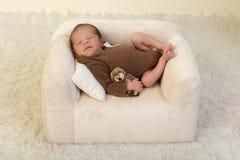 Sleepy newborn on white couch stock photo