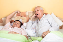 Sleepy senior couple yawning in bed Stock Images