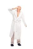 Sleepy senior man in a white bathrobe yawning Royalty Free Stock Image