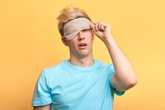 Sleepy tired exhausted man taking off the sleeping mask. royalty free stock photography