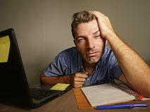 Sleepy tired and exhausted man working on laptop computer accounting taking notes on notepad overworked suffering depression stock photography