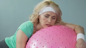 Sleepy tired middle-aged woman lying on fitness ball after active workout