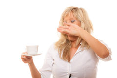 Sleepy tired woman yawning holds cup of coffee Stock Image