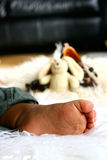 Sleepy toes. A baby's foot as he lays asleep on sheep skin rug with some baby toys in background Royalty Free Stock Photos