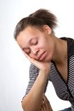 Sleepy Woman. Sleepy African American woman rests with her head in the palm of her hand and eyes closed Stock Images