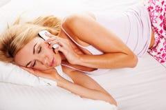 Sleepy woman answering a phone call Stock Photography