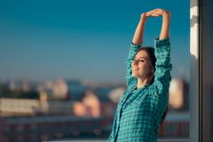 Girl in pajamas waking up early and stretching in morning light Royalty Free Stock Image