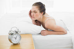 Sleepy woman in bed with alarm clock in foreground Royalty Free Stock Photography