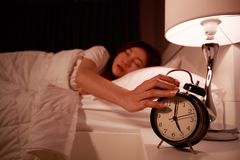 Sleepy woman in bed with eyes closed extending hand to alarm clo Stock Photos