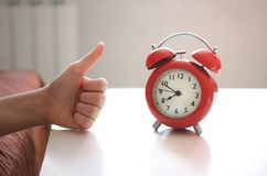 Awakining with alarm clock. Sleepy woman in the bed is showing a thumbs up gesture by her hand to a red alarm clock on the table at morning time. Punctuality stock image