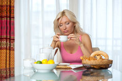 Sleepy woman at breakfast table Royalty Free Stock Images