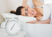 Sleepy woman covering ear with hand in bed Royalty Free Stock Images