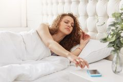 Sleepy woman with curly hair turns off alarm on smart phone, wak. Es early up in morning, tries to get up, doesn`t want to go for work, feels comfortable at bed stock photography