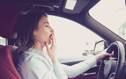 Sleepy woman driving her car after long hour trip isolated street background. Sleep deprivation and accident concept Stock Images