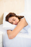 Sleepy woman in her bed Stock Photos