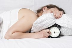 Sleepy woman hides an alarm clock under the pillow. girl sleeps in bed in early morning and hears an alarm bell. Get up on alarm clock in morning. Wake up Stock Photos