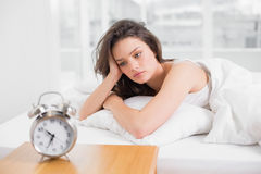 Sleepy woman looking at alarm clock on bedside table Stock Image