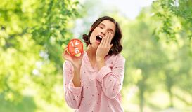 Sleepy woman in pajama with alarm clock yawning. People and bedtime concept - sleepy young woman in pajama with alarm clock showing half past six yawning over royalty free stock photography