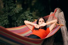 Sleepy Woman Relaxing in Hammock on Summer Vacation. Lazy tourist relaxing outdoors yawning and feeling sleepy royalty free stock image