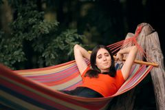 Sleepy Woman Relaxing in Hammock on Summer Vacation. Lazy tourist relaxing outdoors yawning and feeling sleepy stock images