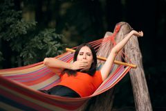 Sleepy Woman Relaxing in Hammock on Summer Vacation. Lazy tourist relaxing outdoors yawning and feeling sleepy royalty free stock photography