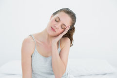 Sleepy woman sitting in bed Stock Image