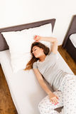 Sleepy woman sleeping in the bed. Stock Image