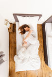 Sleepy woman sleeping in the bed. Mornings people concept. Sleepy woman sleeping in the bed. Attractive lady changing sleep positions Royalty Free Stock Image