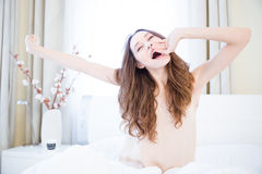 Sleepy woman stretching and yawning on bed Royalty Free Stock Image