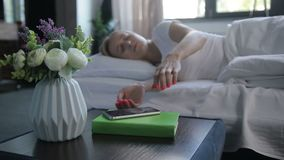 Sleepy woman turning off mobile alarm clock. Beautiful calm blonde woman waking up to the sound of alarm clock on mobile phone in morning. Charming sleepy girl stock video